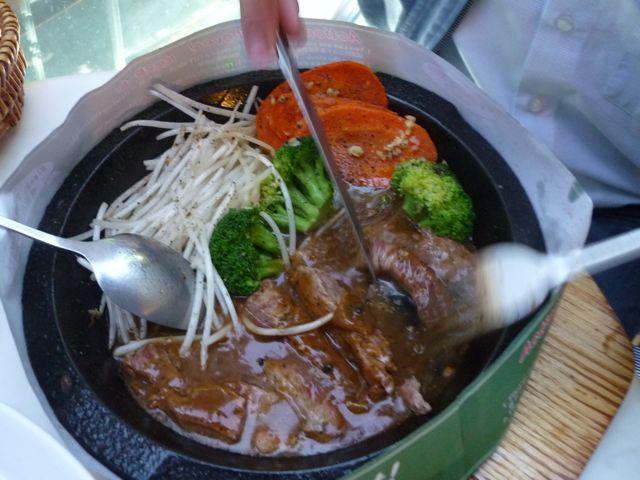 Fleisch gart in heißer Pfanne am Tisch